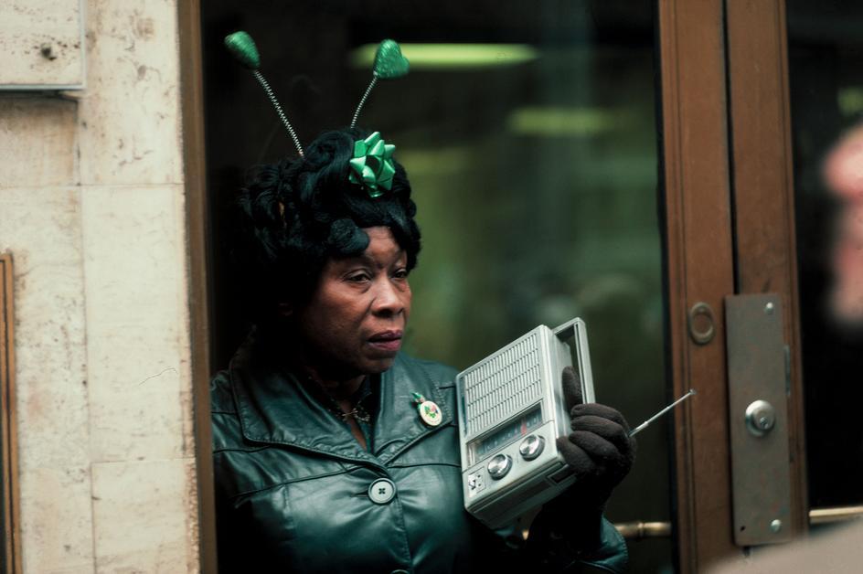 Женщина слушает радиоприемник во время парада в день Святого Патрика