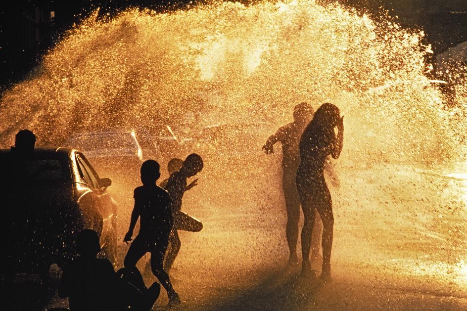 Дети играют в брызгах воды из гидранта на одной из улиц Гарлема
