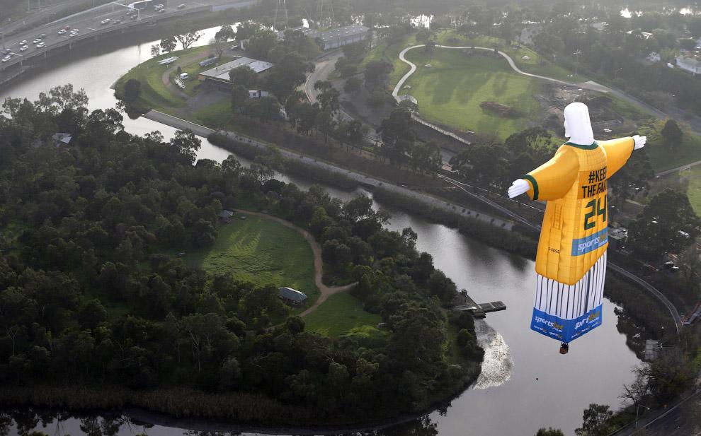 Воздушный шар в виде фигуры бразильской статуи Христа Спасителя в футбольной форме проплывает над Мельбурном