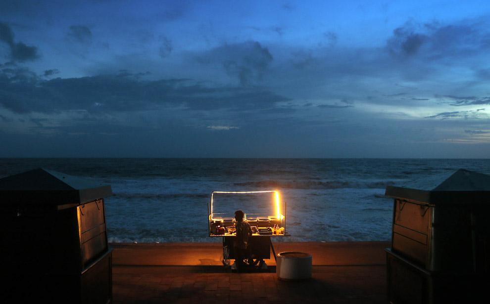 Торговец закусок ждет клиентов на берегу
