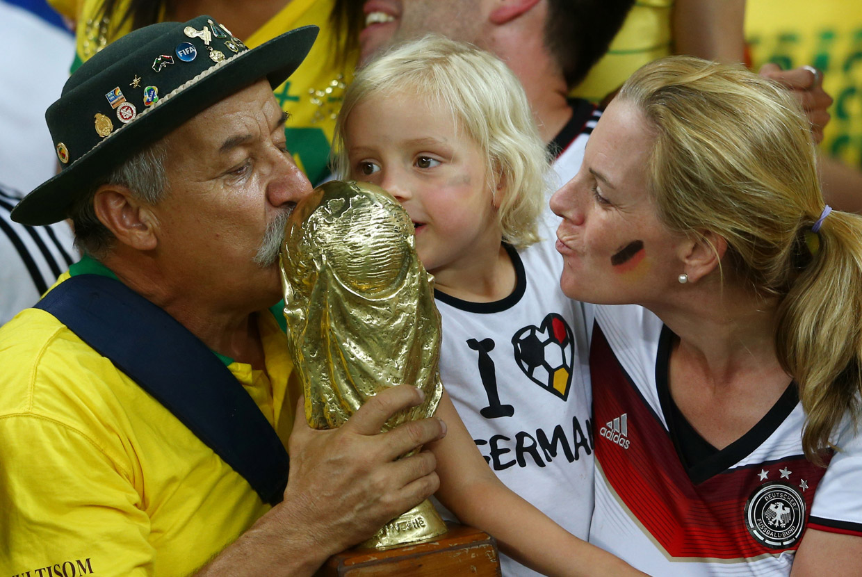 Необычная фотография: добродушный болельщик сборной Бразилии с немецкими болельщиками после поражения от Германии со счетом 7:1