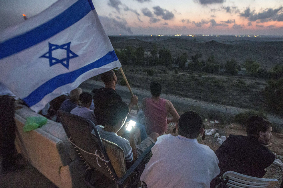 Жители южной израильского города Сдерот наблюдают с холма за боями в секторе Газа