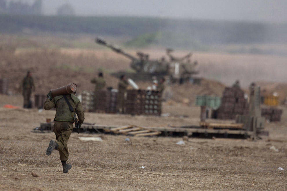 Израильские солдаты перезаряжают пушку на границе с сектором Газа