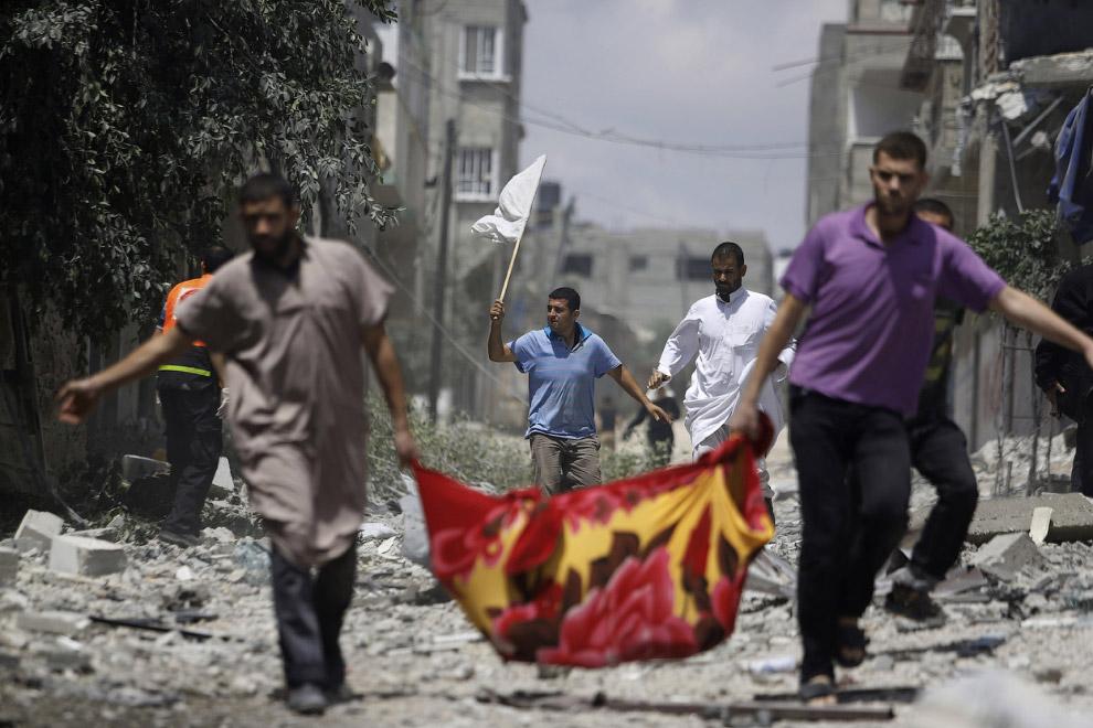 Палестинцы несут то ли раненого, то ли убитого