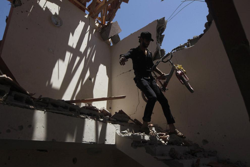 Палестинец с велосипедом в разрушенном доме