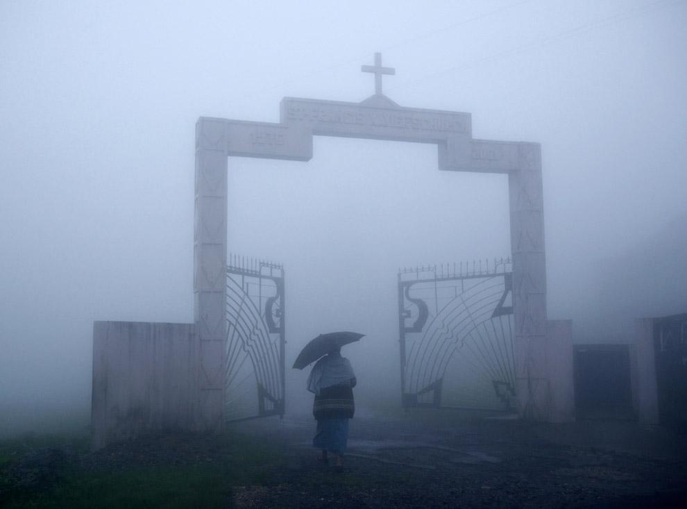 Воскресенье массы в католической церкви. Прихожане идут под проливным дождем