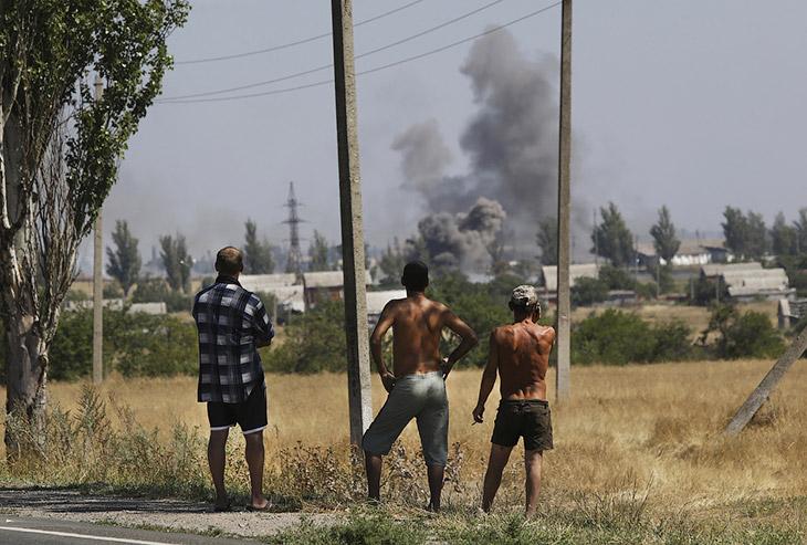 Местные жители и дым от обстрела в городе Новоазовске на востоке Украины