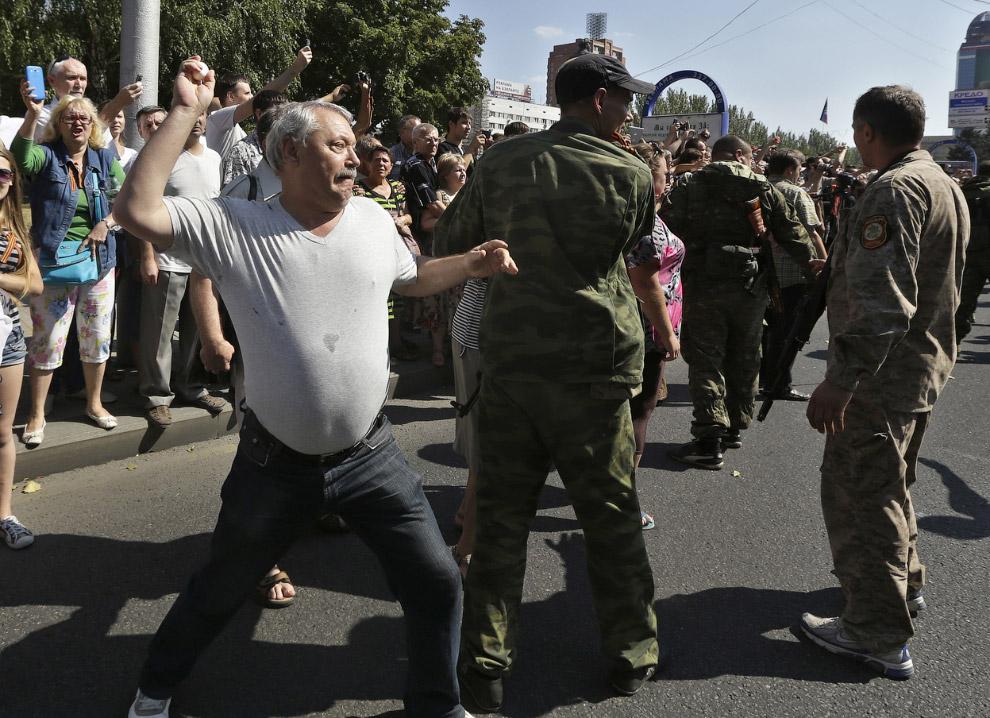 Человек бросает яйцо в украинских солдат во время «парада военнопленных» в Донецке