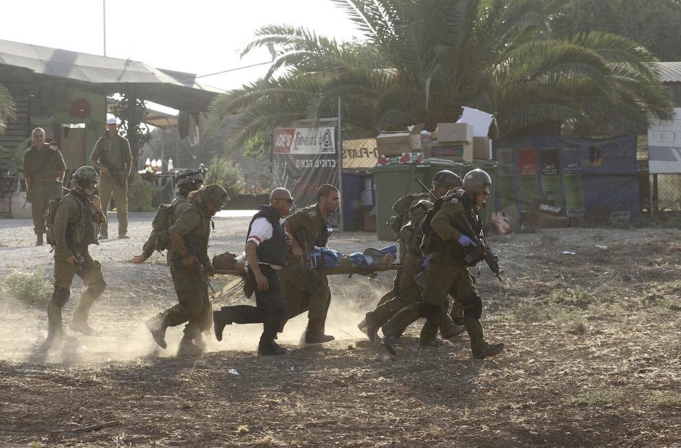 Израильские солдаты несут своего раненого товарища