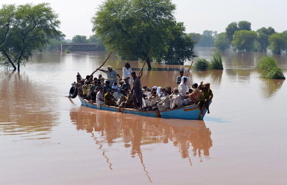 Пакистанцы вывозят жителей затопленных домов на лодке