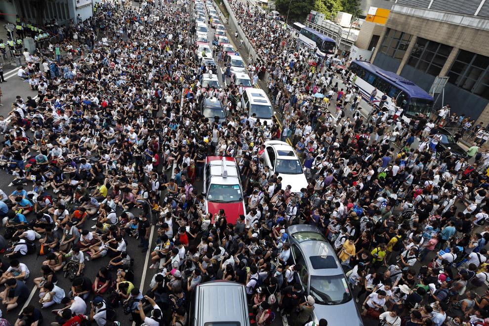 Десятки тысяч демонстрантов блокируют движение на главной дороге, ведущей у Центральному району Гонконга