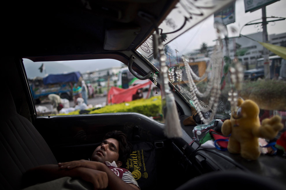 Пакистанский протестующий уснул в автомобиле, припаркованном перед зданием парламента в Лахоре