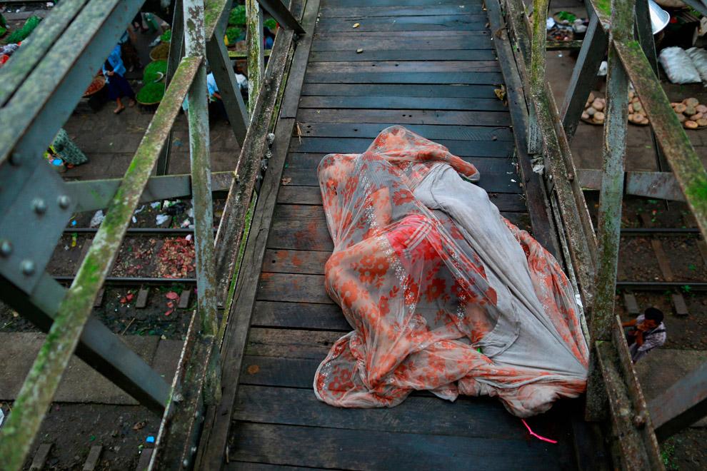 Спящие под москитной сеткой на мосту над железнодорожной станцией около Янгона, Мьянмы