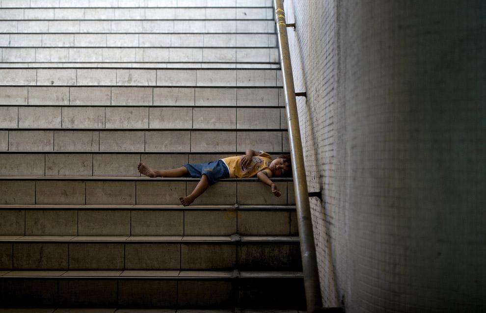 Ребенок спит на ступеньках подземного перехода в Маниле, Филиппины