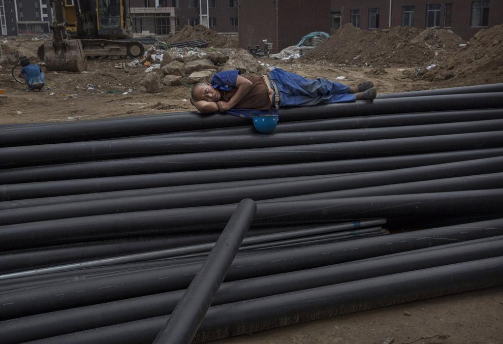 Китайский строитель спит на трубах на строительной площадке нового жилого комплекса в Пекине, Китай