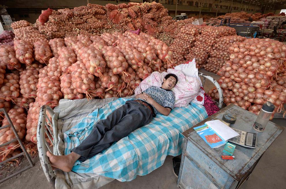 Продавец лука на овощном оптовом рынке в провинции Шаньси, Китай