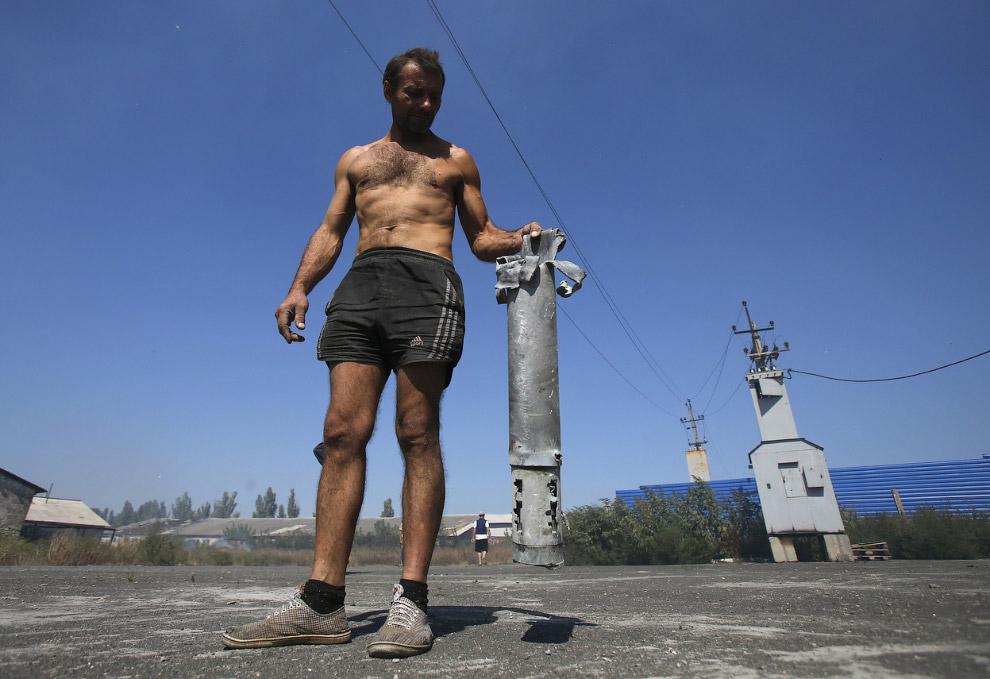 Местный житель показывает оболочку снаряда, упавшего в селе Спартак около Донецка