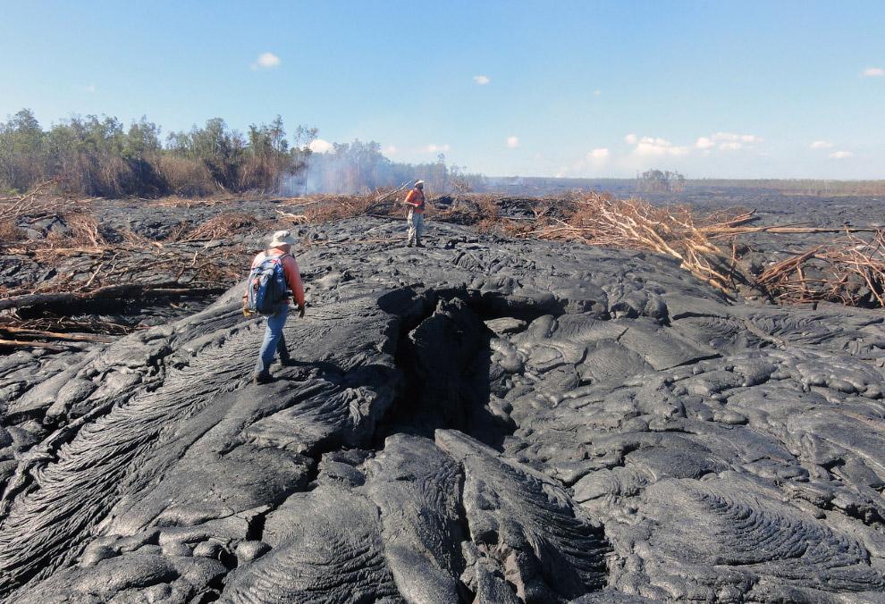 Геологи ходят по поверхности потока лавы