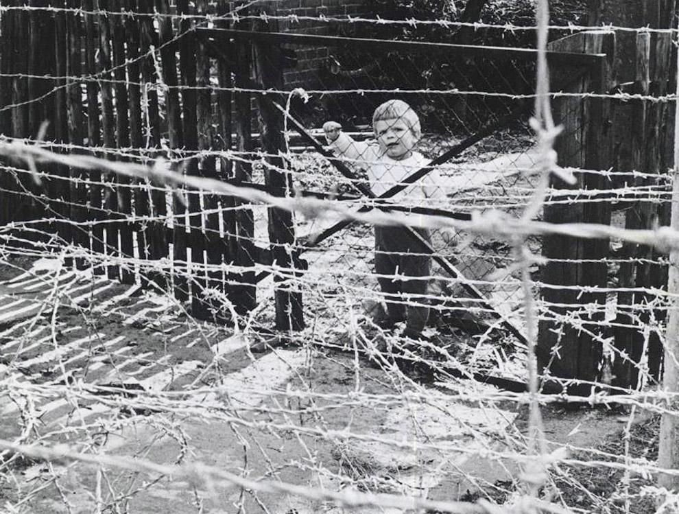 Девочка из Восточной Германии за колючей проволокой Берлинской стены