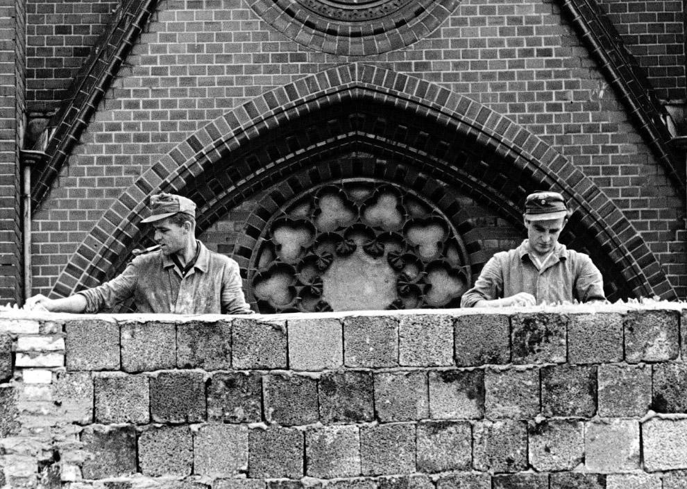 Рабочие возводят Берлинскую стену. Сзади видна церковь