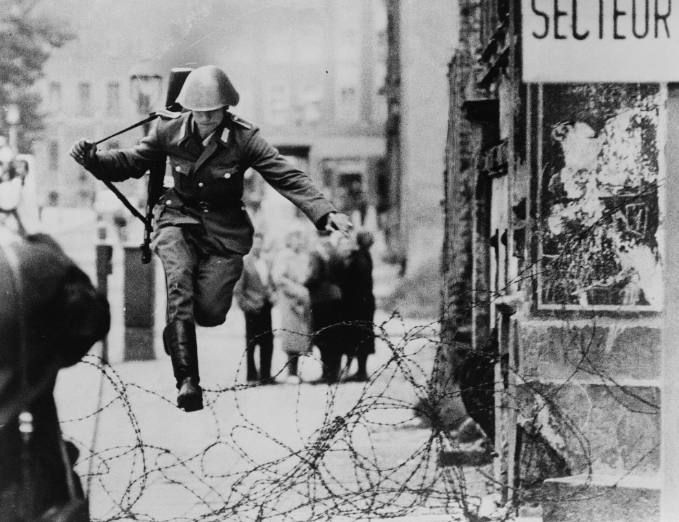 19-летний военнослужащий пограничных войск Конрад Шуман перепрыгнул через мотки колючей проволоки