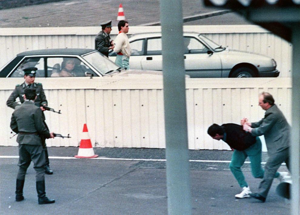Двое жителей Восточного Берлина прыжками пытаются преодолеть пограничные барьеры