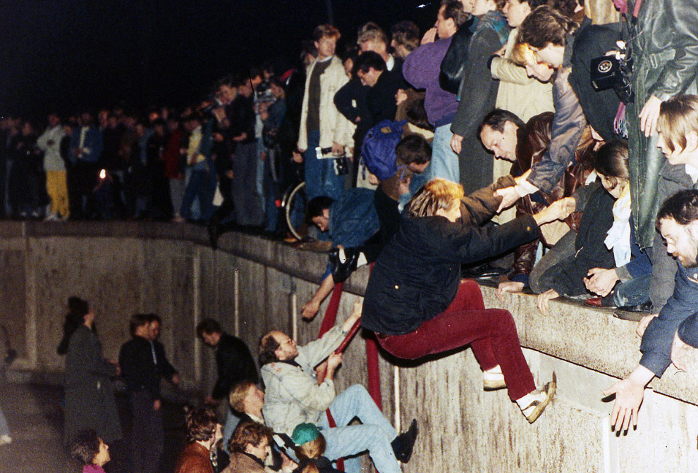 10 ноября 1989, около Бранденбургских ворот. Жители одной части Берлина взбираются на Стену, жители другой стороны города им помогают