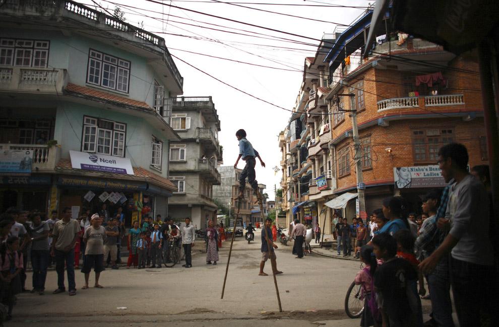 Мальчик на деревянных ходулях на улице в Катманду