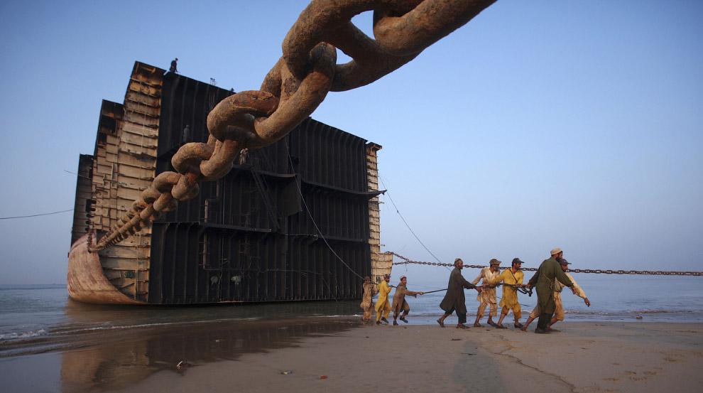 Рабочие тянут трос, чтобы отделить часть от корабля