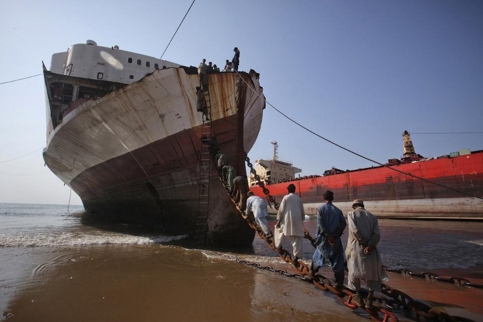 Рабочие взбираются на корабль по цепи, Гаддани, Пакистан