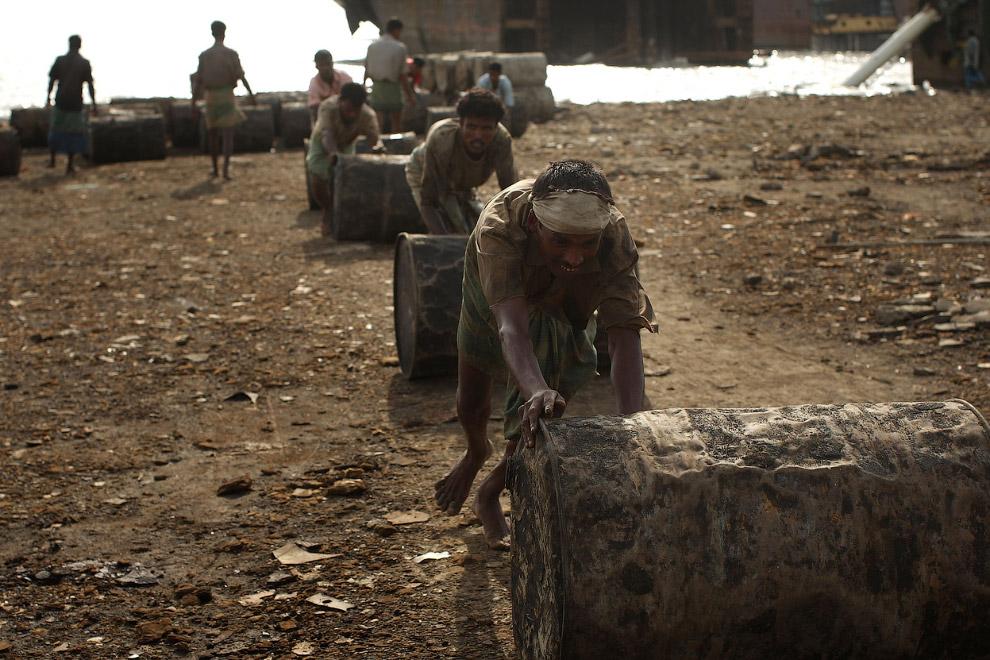 Рабочие выкатывают нефтяные бочки с корабля на берег