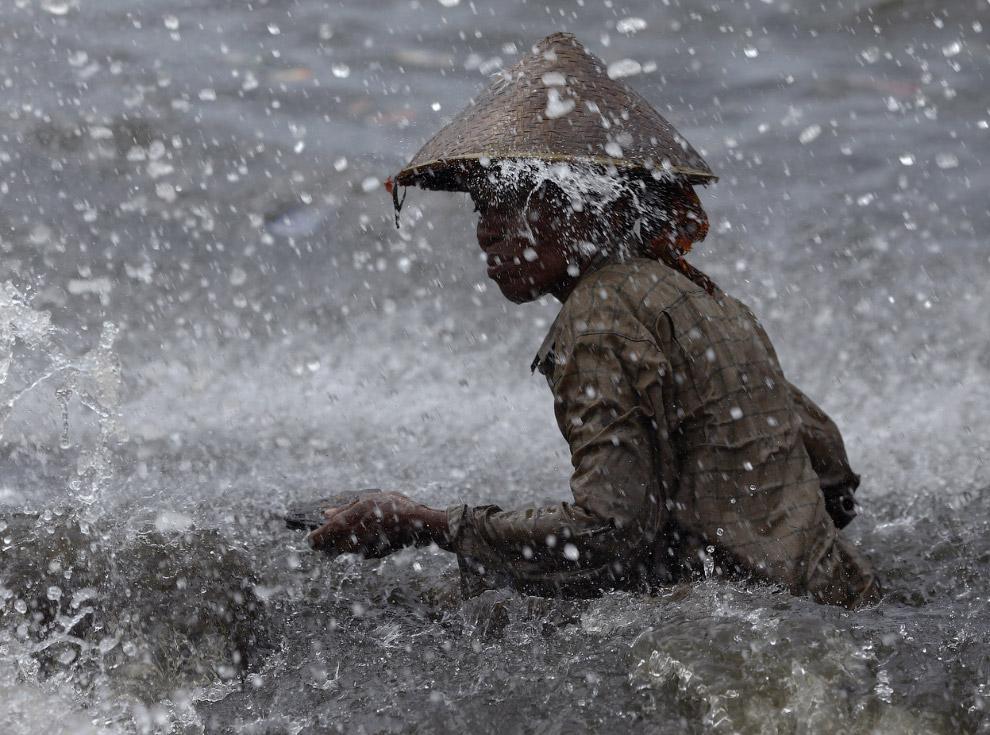 Женщина собирает ржавые куски металла на пляже под дождем