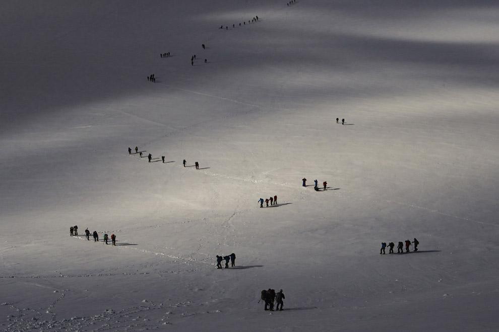 Альпинисты взбираются на ледник между Швейцарией (справа) и Италией (слева) на знаменитом альпийском курорте Церматт