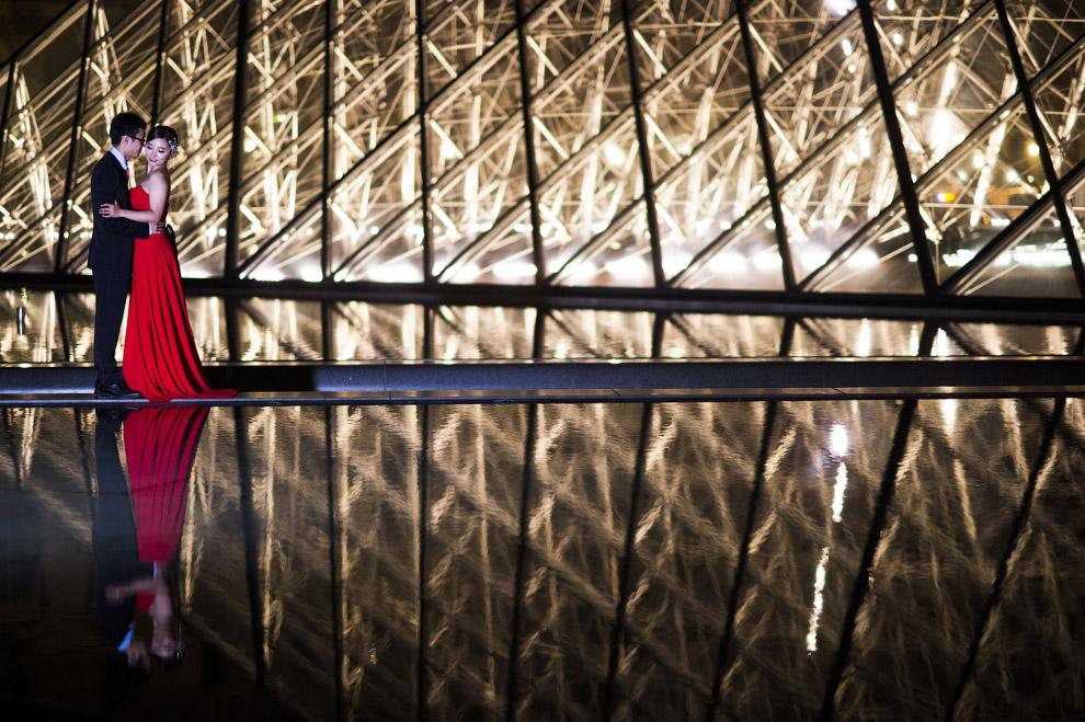Стильная фотография молодоженов около входа в Лувр в Париже