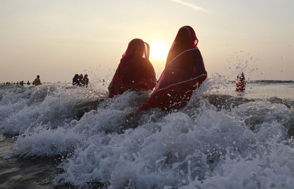 Индийские женщины молятся в Аравийским морем во время заката, Мумбаи, И
