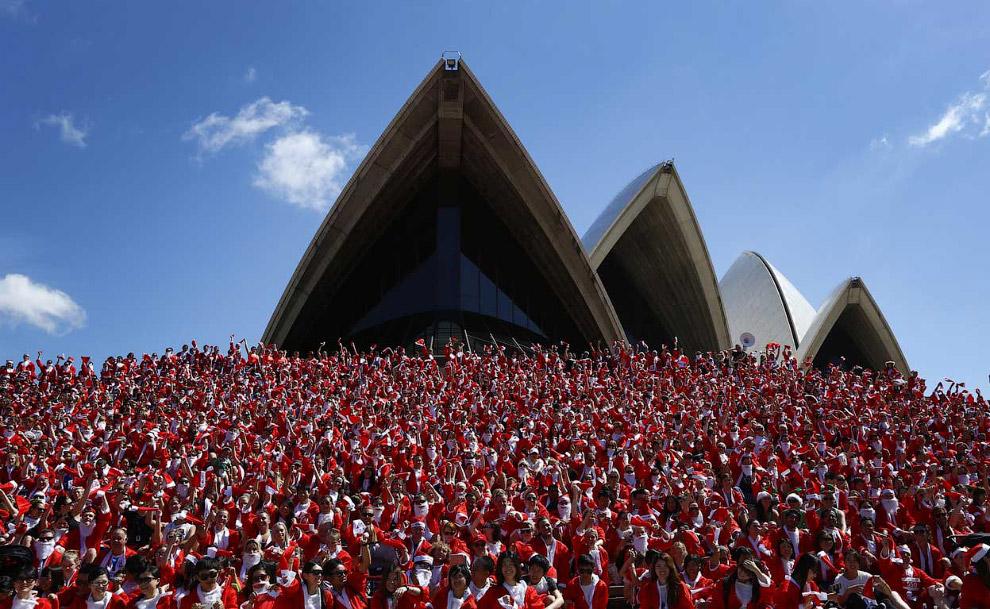 Бегуны в костюмах Санта-Клаусов перед Сиднейским оперным театром
