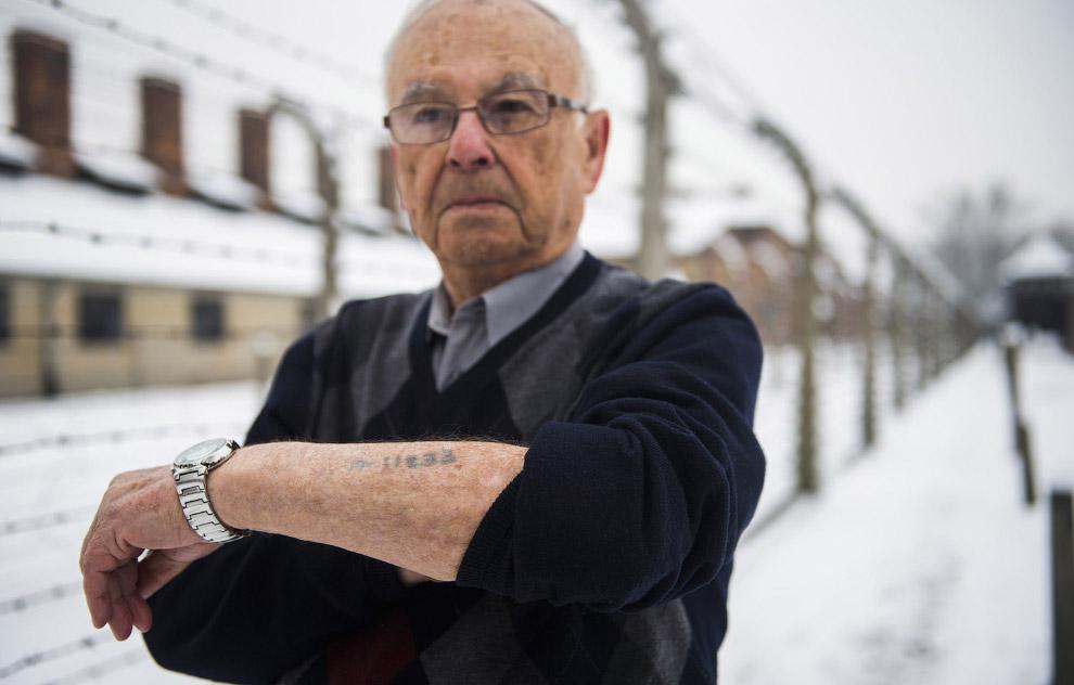 Выживший в лагере, показывает его номер заключенного на татуировке