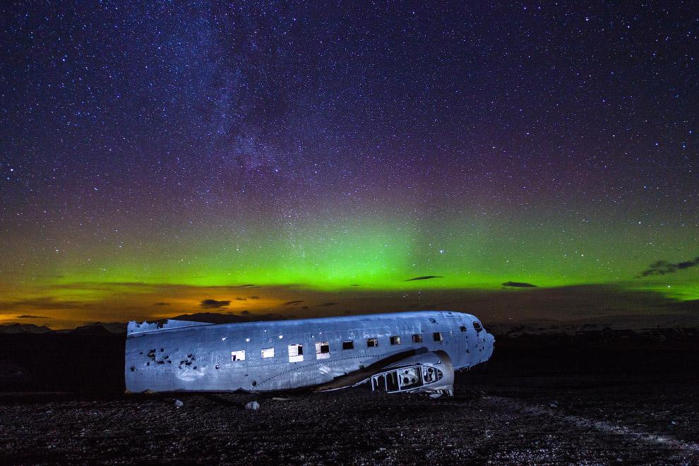 Самолет и северное сияние на вулканическом пляже в Исландии