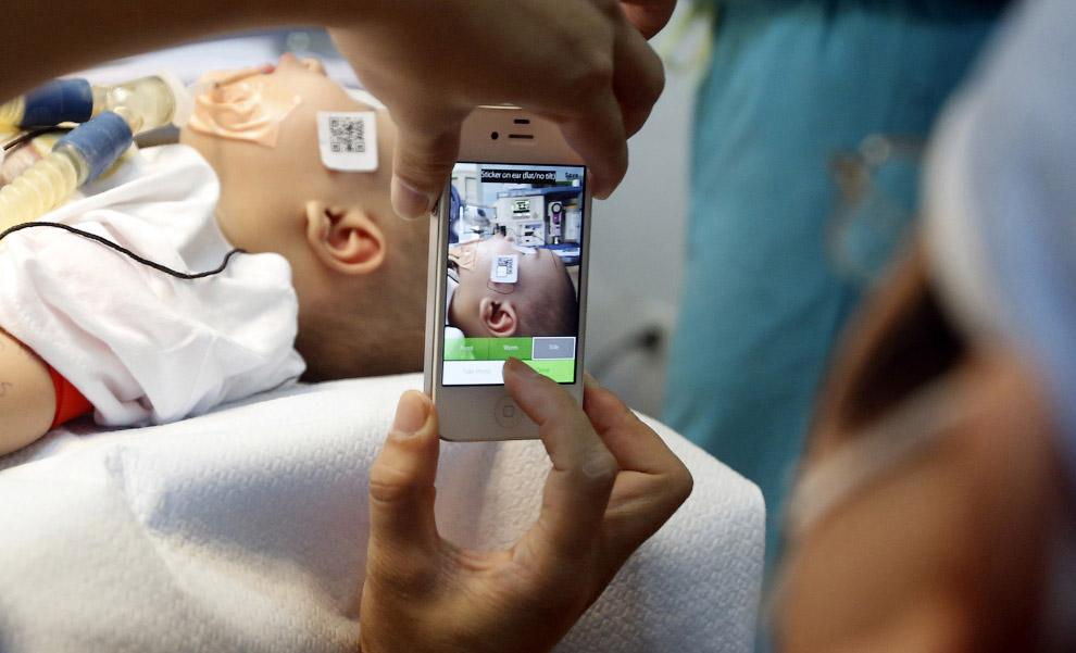 Доктор снимает на смартфон больного мальчика в госпитале в Ханое, Вьетнам