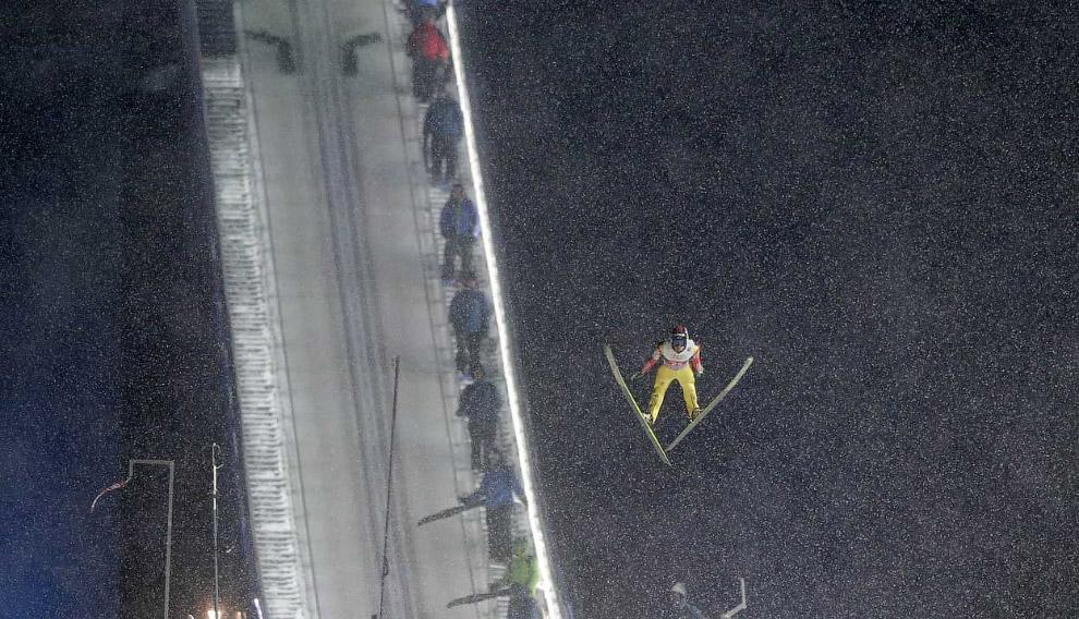Летящий лыжник с трамплина на соревнованиях в Оберстдорфе, Германия