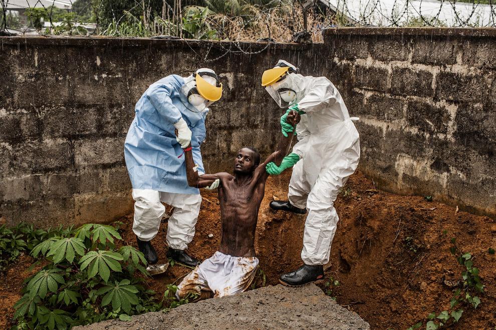 Медицинский персонал лечебного центра в Сьерра-Леоне забирают обратно в изолятор сбежавшего больного, заразившегося вирусом Эбола