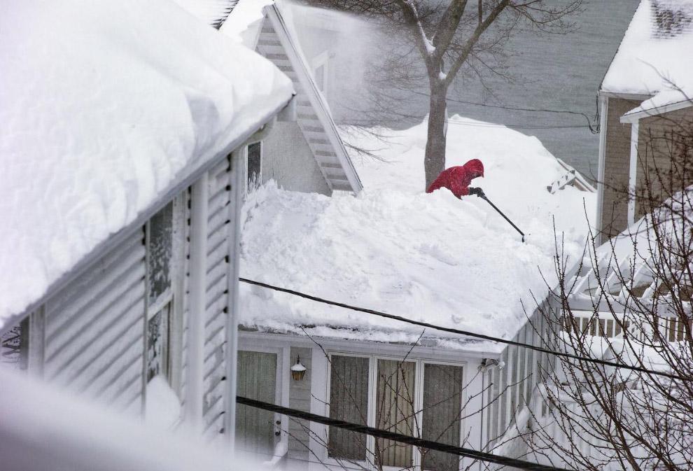 Местные жители расчищают крыши домов