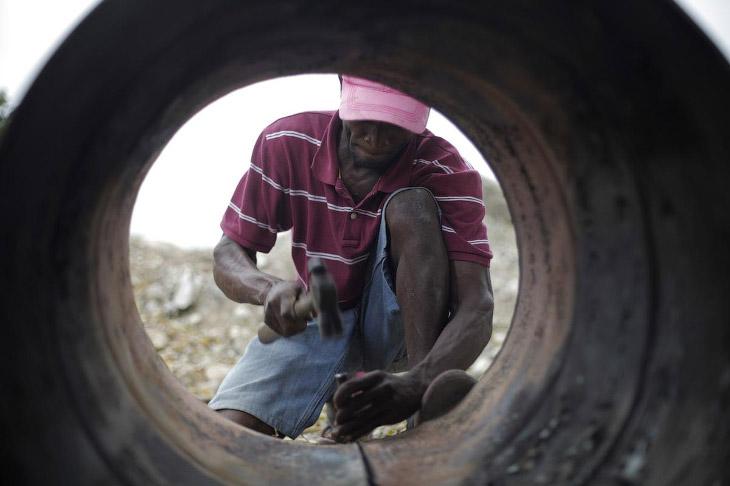 Местный житель разбирает нефтяной баррель на окраине Порт-о-Пренс