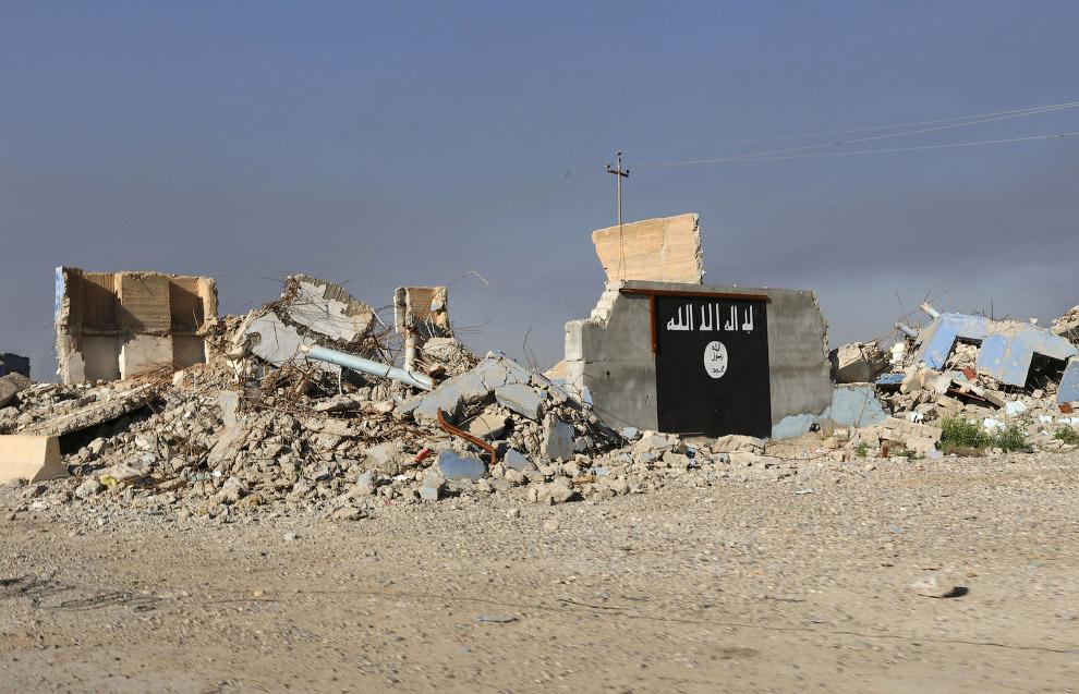 Разрушенное здание и флаг радикальной группировки «Исламское государство»