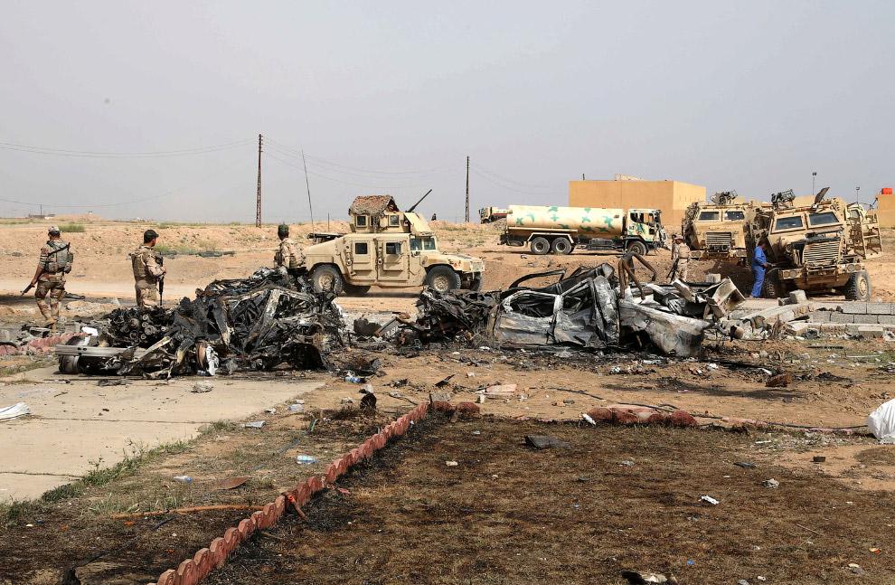 Иракские солдаты осматривают место взрыва заминированного автомобиля
