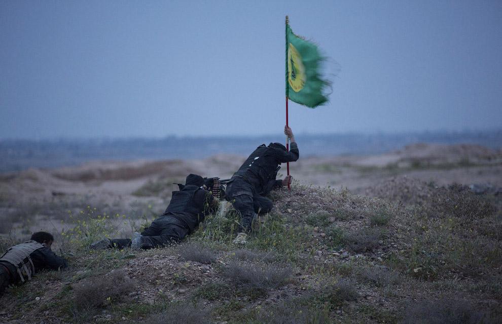 Бойцы шиитской группировки пытаются воткнуть шиитский флаг в землю на окраине Тикрита