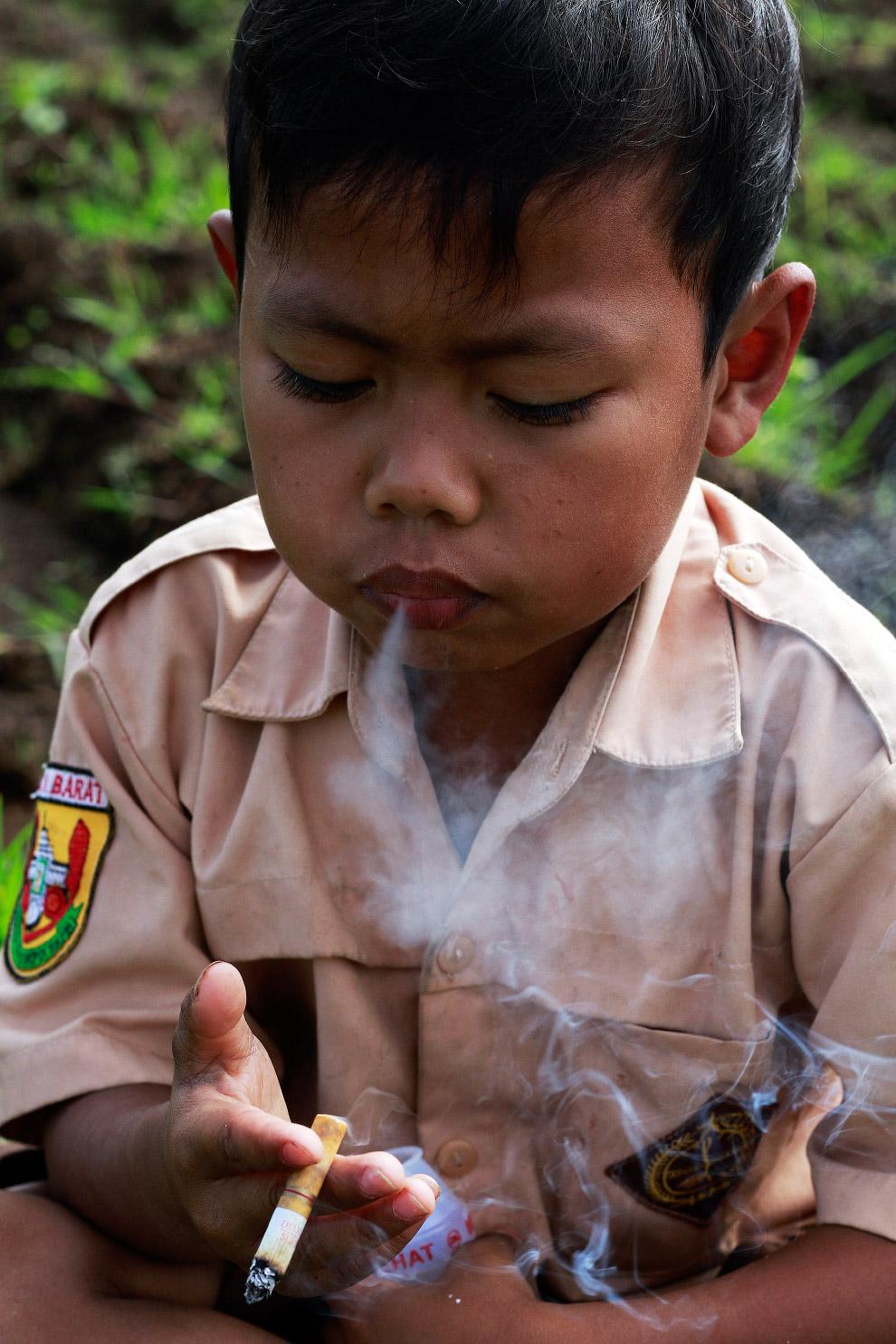 Вот он курит в рисовом поле около дома