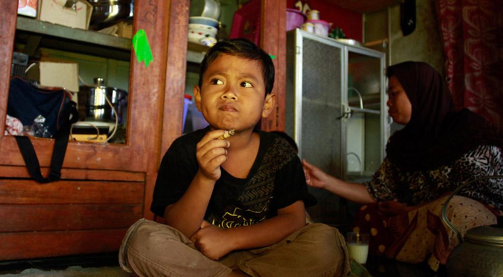 Семилетний Дихан с сигаретой дома, сзади — мама