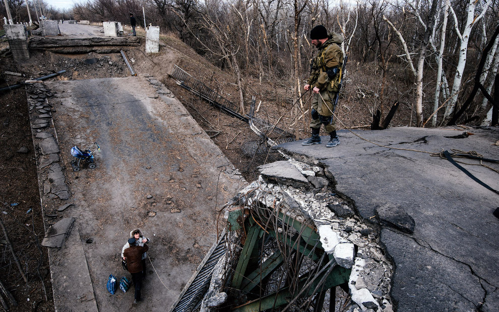 Ополченцы помогают паре забраться на разрушенный мост через реку Северский Донец на востоке Украины