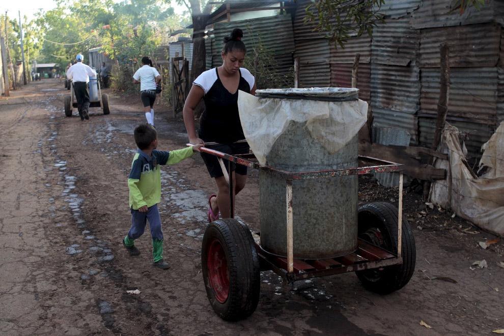 Люди толкают телеги с водой из колодца к себе по домам на окраине Манагуа